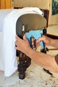 Upholsterer repairing an old armchair using a stapler